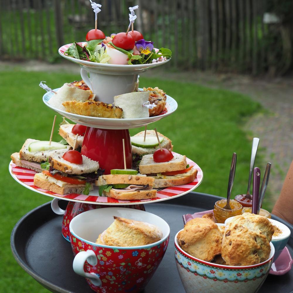 De high tea: een etagere vol lekkers, op een dienblad.