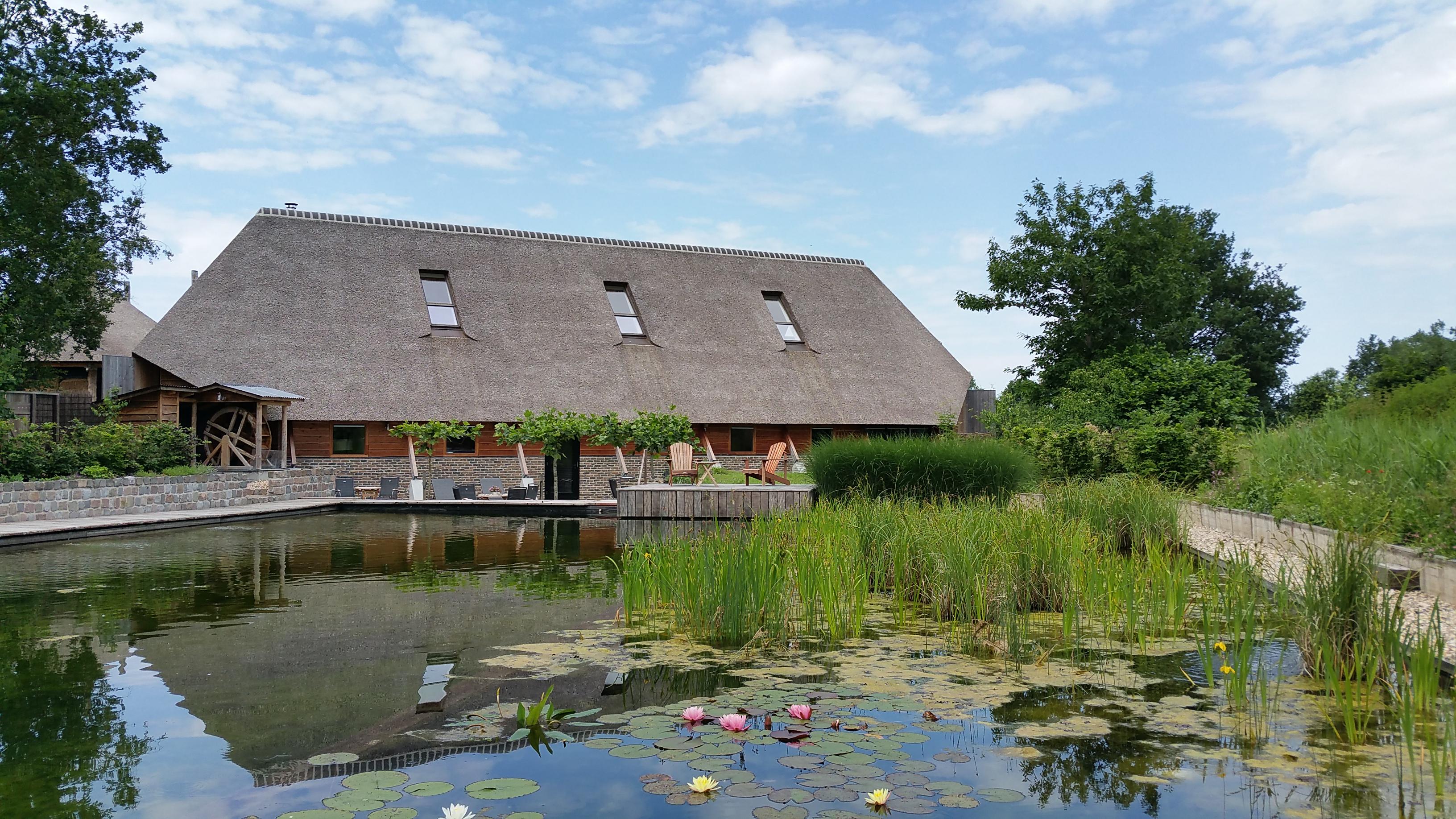 Samen een dagje uit naar een kleinschalige spa of wellness: een boerderij met rieten dak met zwemvijver ervoor.