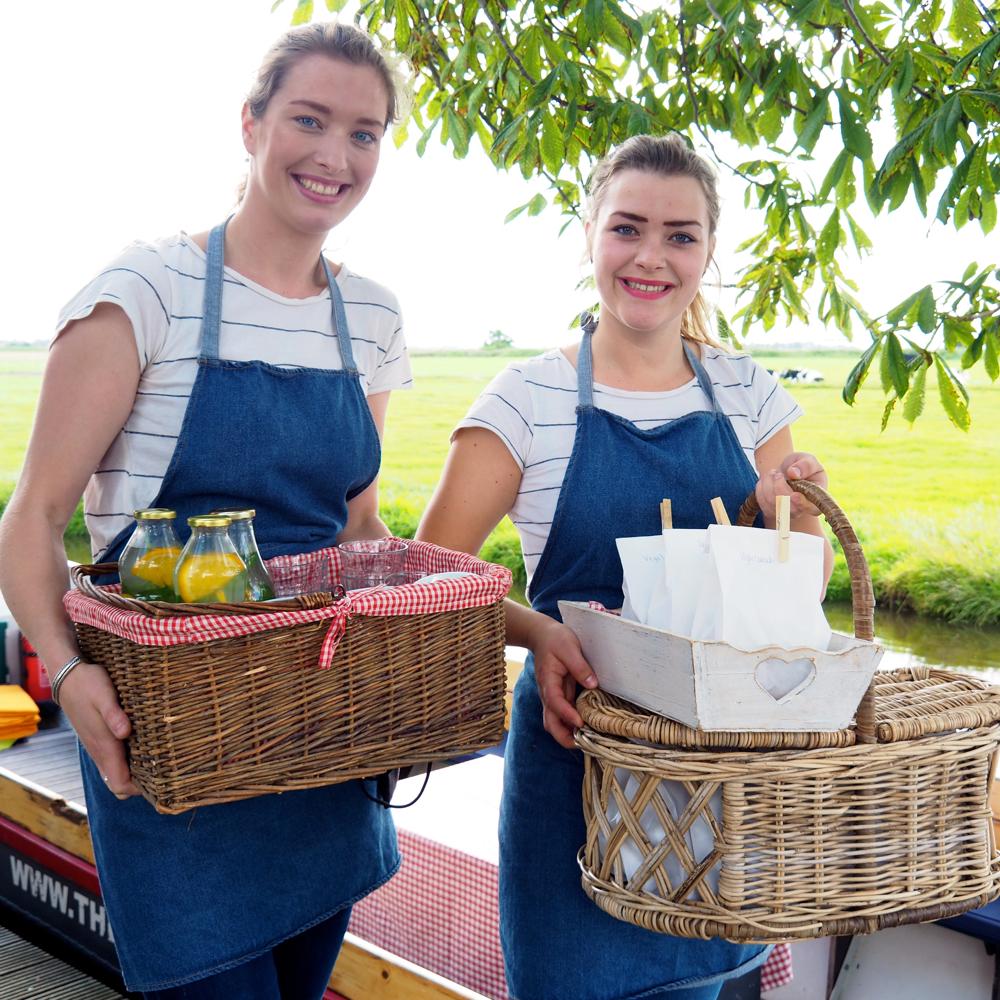 2 dames met blauwe schorten aan die elk een goed gevulde picknickmand vasthouden bij fluisterbootjes.