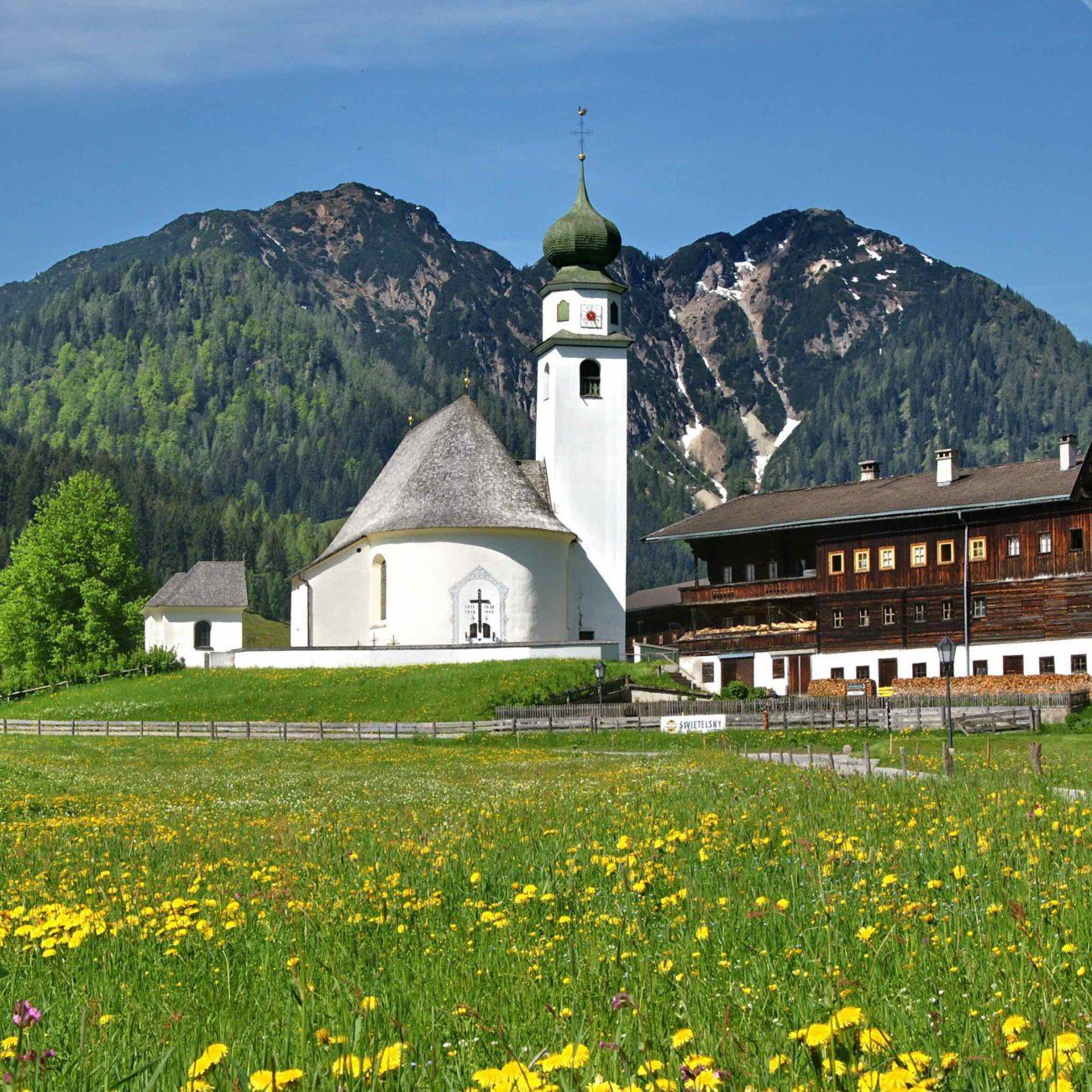 Een typisch Oostenrijks landschap met bloemenweide, kerkje en bergen.