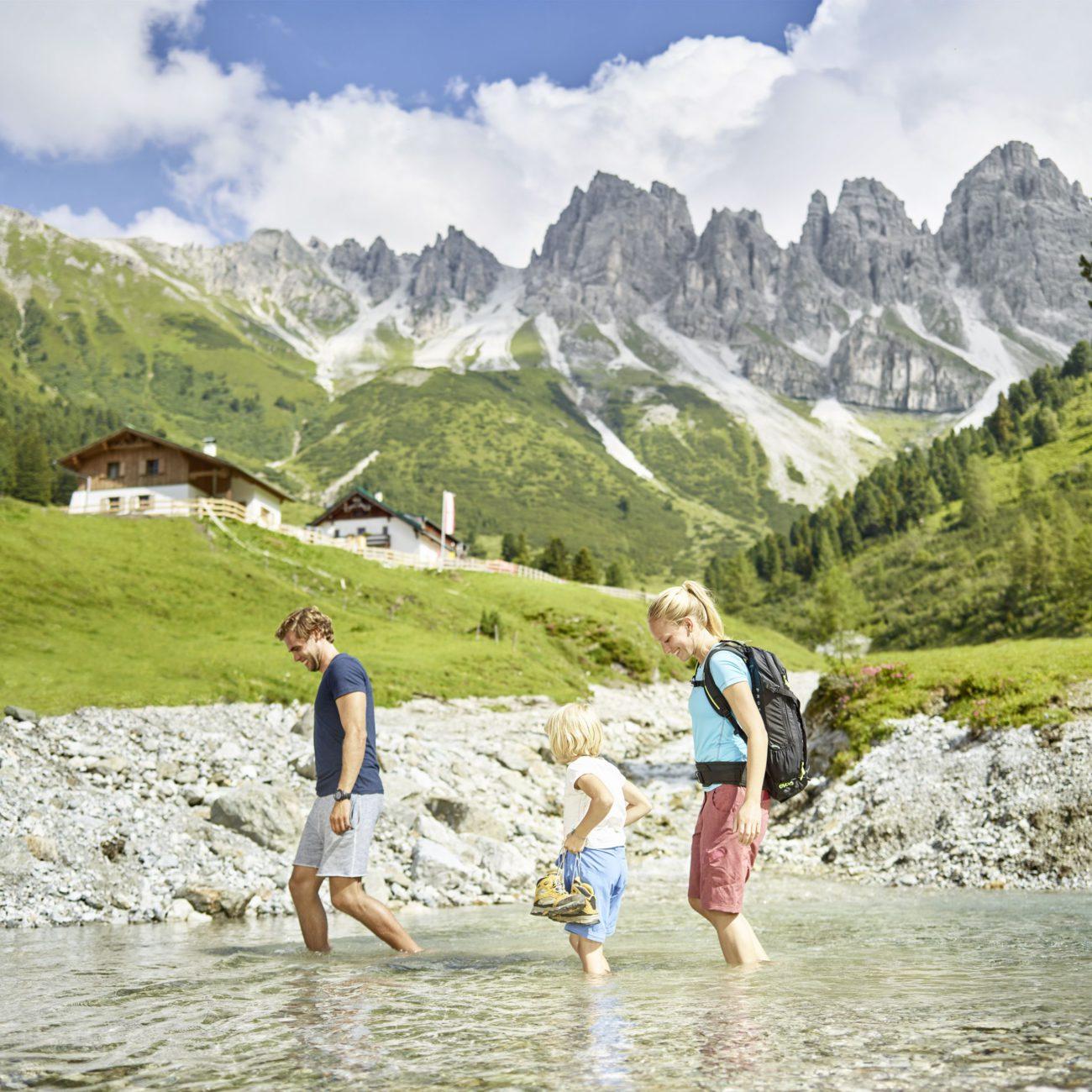 Tijdens je vakantie in Oostenrijk bergwandelingen maken en afkoelen in de beek. Een gezin van drie personen in het water
