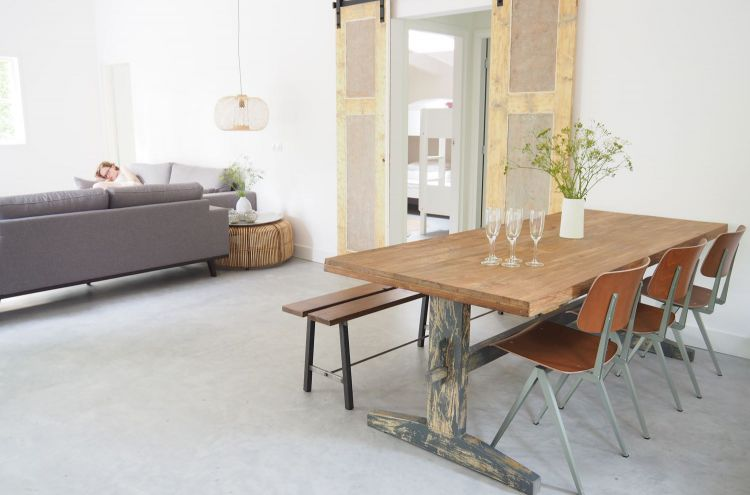 Eethoek met stoere eettafel en doorkijk naar de zithoek met grijze bank in vakantiehuis Friesche Duin.