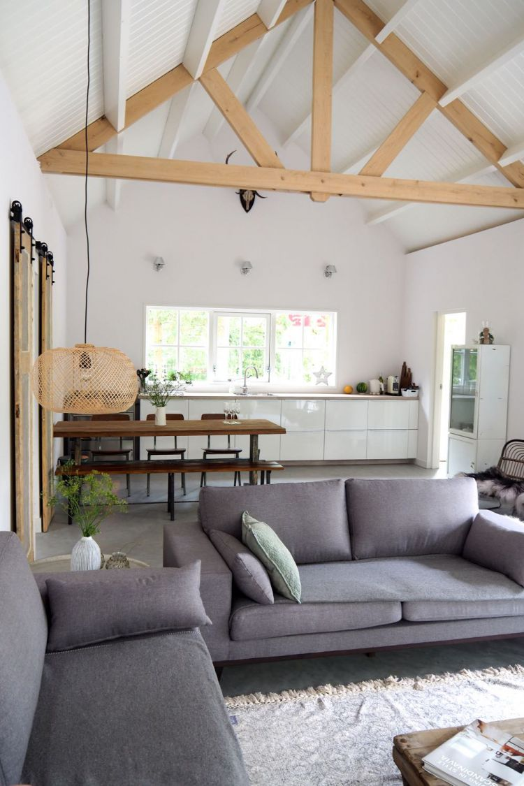 Boshuis in Friesland met een Scandinavisch interieur: grijze banken, een betonnen vloer, witten muren, stoere houten balken en een witte keuken.