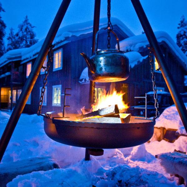 Een vuurtje in een driepot in de sneeuw met op de achtergrond het hotel