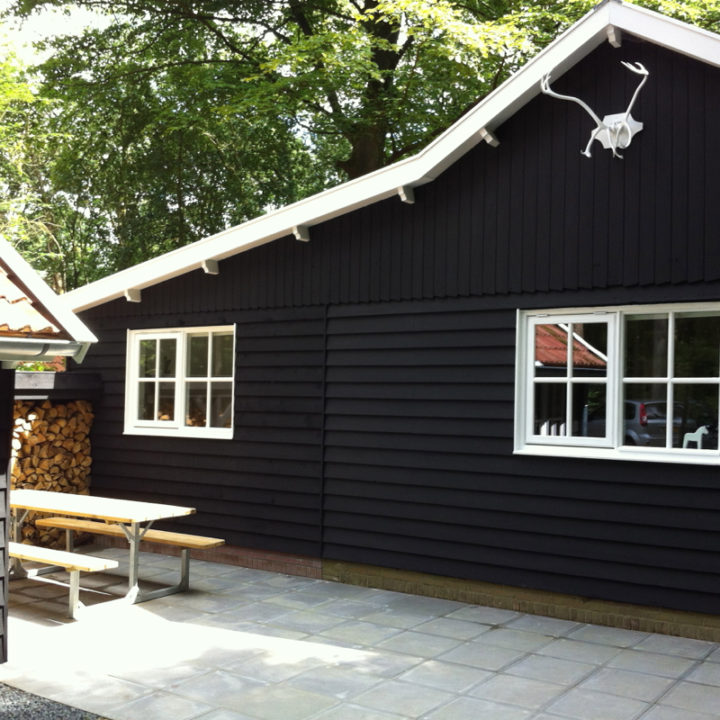 De buitenzijde van het zwarte houten Boshuis.