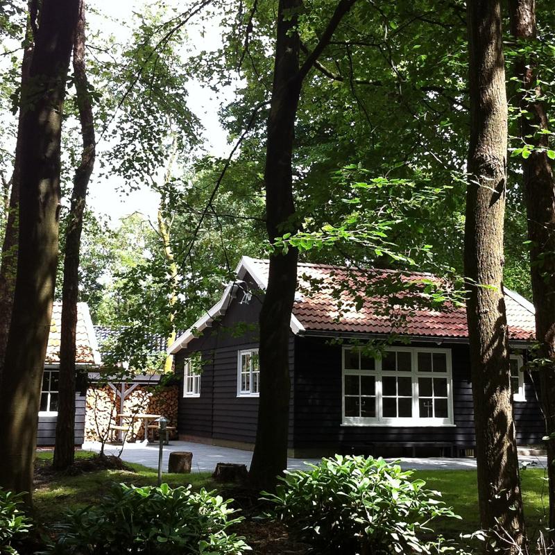 Een zwart houten boshuis in de bossen van Appelscha.