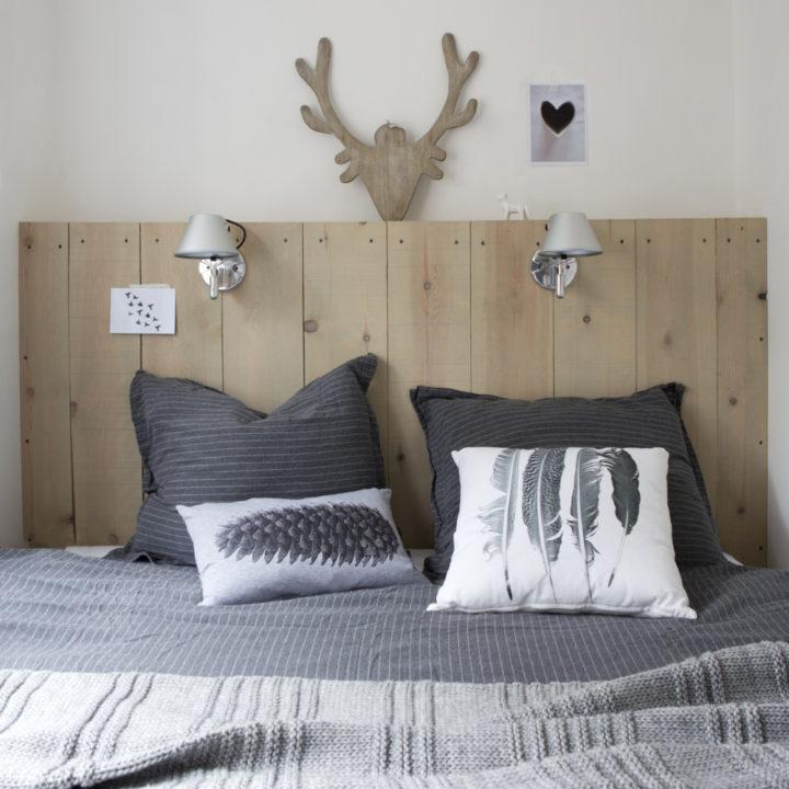 Slaapkamer in Boshuis Nij Hildenberg met grijze plaid en mooie kussens.
