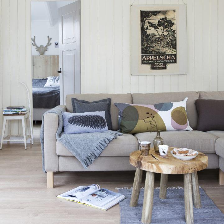 Lichtkleurige bank met kussens en plaid en houten tafeltje ervoor in Boshuis Nij Hildenberg.