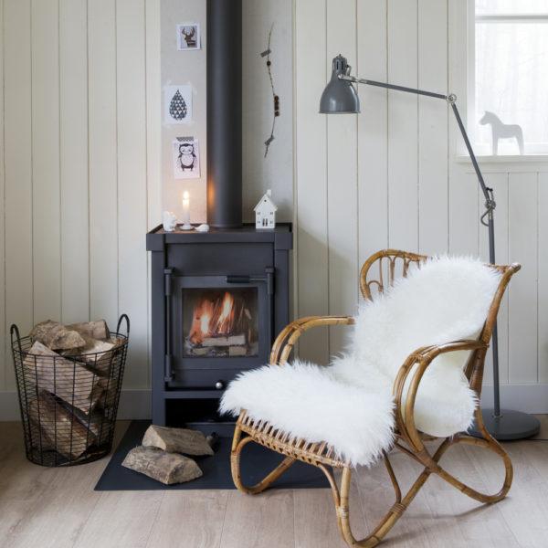 Brandende houtkachel met rotan stoel ervoor met bontje erover in Boshuis Nij Hildenberg