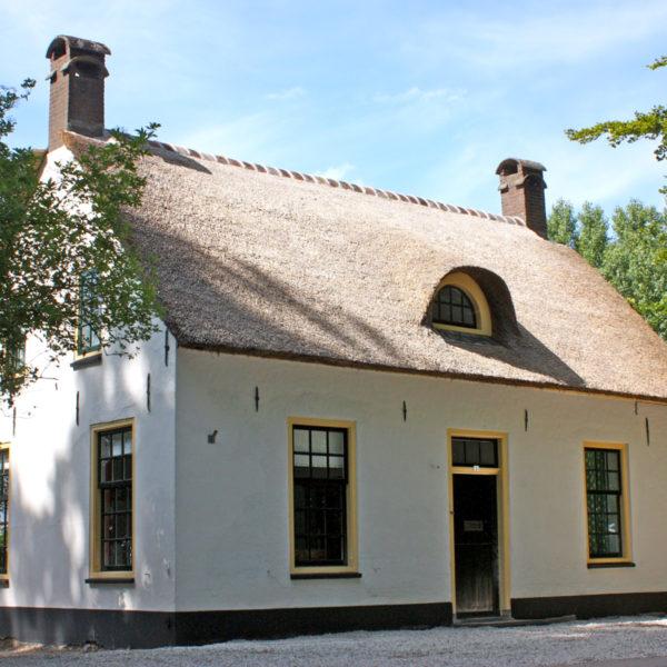 De voormalige jachtopzienerswoning met witgepleisterde muren en rietgedekte kap
