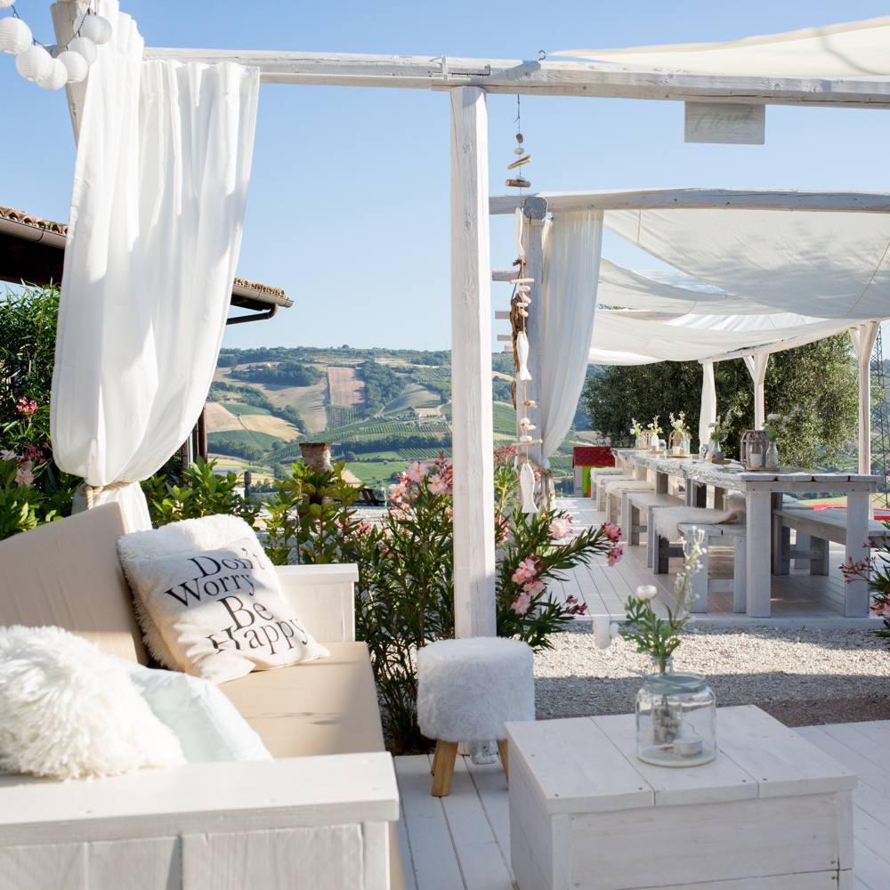 Loungebanken met witte schaduwboeken erboven, in de heuvels van de Italiaanse Le Marche