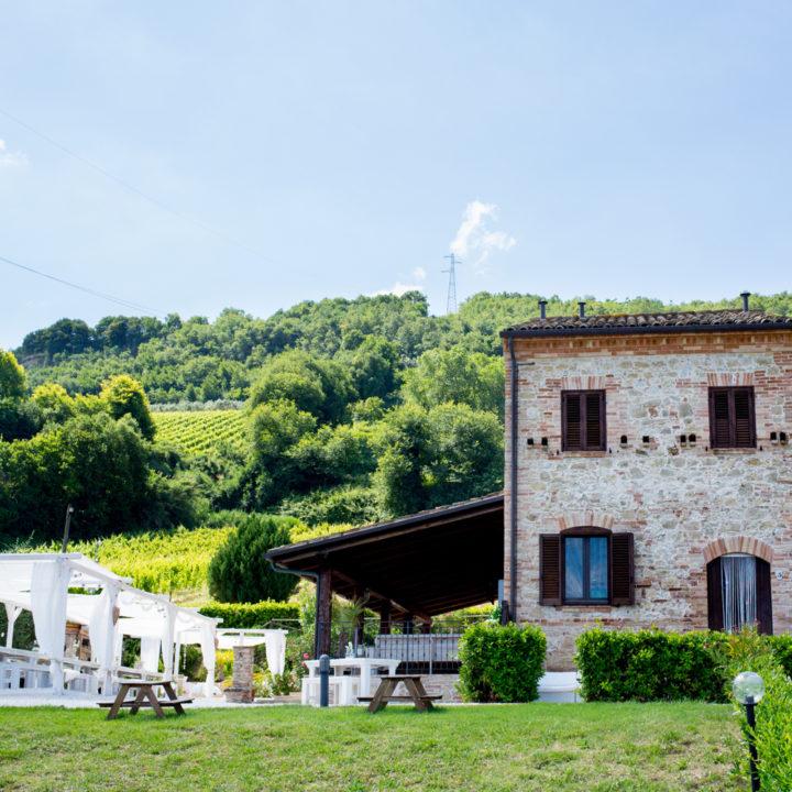 Italiaans landhuis met overkapping aan de zijkant en lange tafels met wit schaduwdoek.