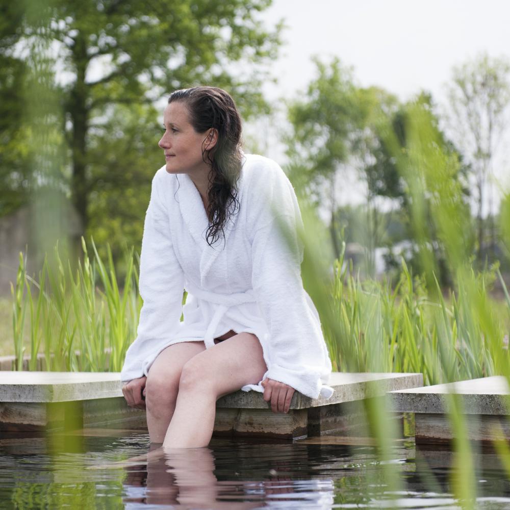 Een dame in witte badjas met haar voeten in een zwemvijver