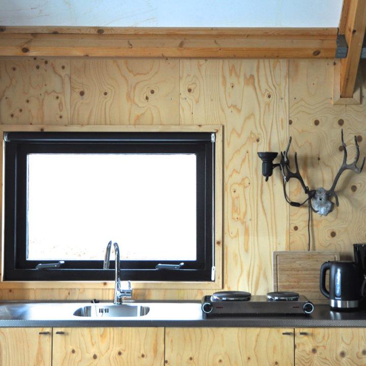 De keuken heeft een koelkast, koffiezetapparaat en elektrische kookplaat.