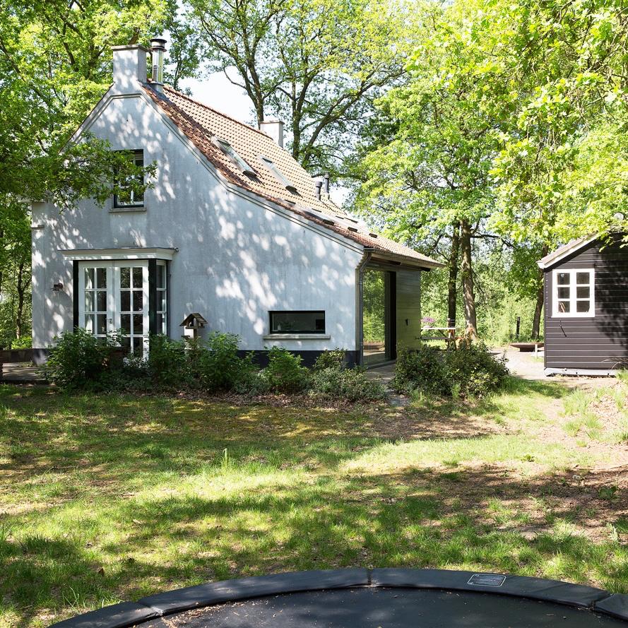 Een idyllisch wit huisje in het bos.