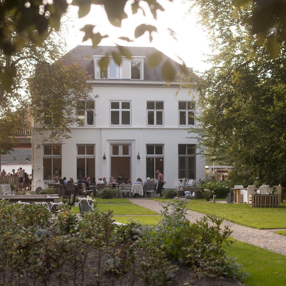 De villa in de mooie parkachtige omgeving en het enorme terras in de tuin.