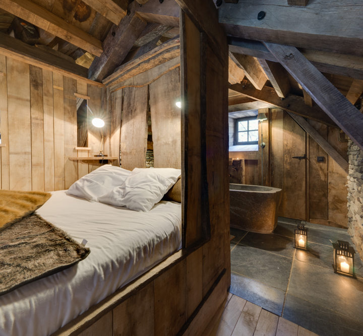 Een houten boomhut met tweepersoons bed, brandende kaarsen en een tobbe als bad