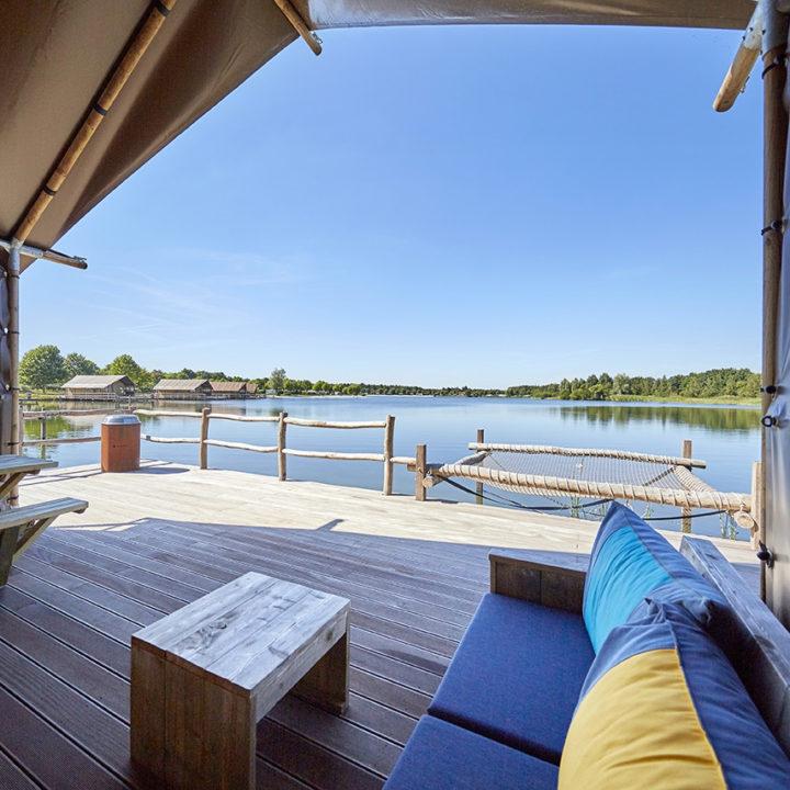 Een comfortabele loungehoek op het terras boven het water.