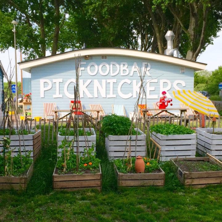 Lichtblauwe gevel met de naam Picknickers in witte letters. Kleurrijke bloemen in de tuin