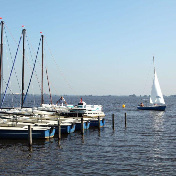 Een rij zeilbootjes aan een steiger in een van de Friese meren