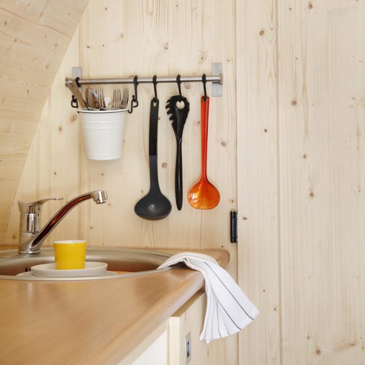 De kitchenette van de comfort en luxe pod beschikt over een spoelbak, koelkast en magnetron.