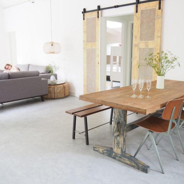 Eettafel van HK Living, betonnen vloer en zithoek met grijze bank in Boshuis Friesche Duin