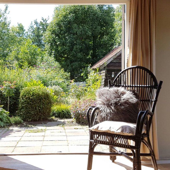 Een rotan stoeltje met kussen voor de openslaande tuindeuren van Het Stalhuys