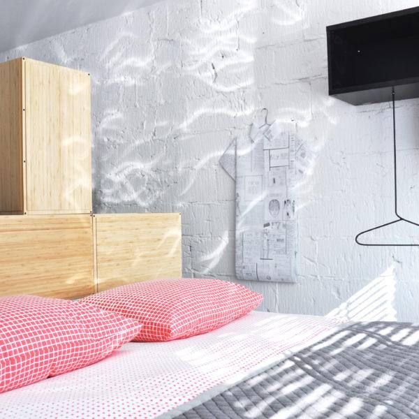 Tweepersoons bed, met rode kussens, een witte wand en zwart kastje