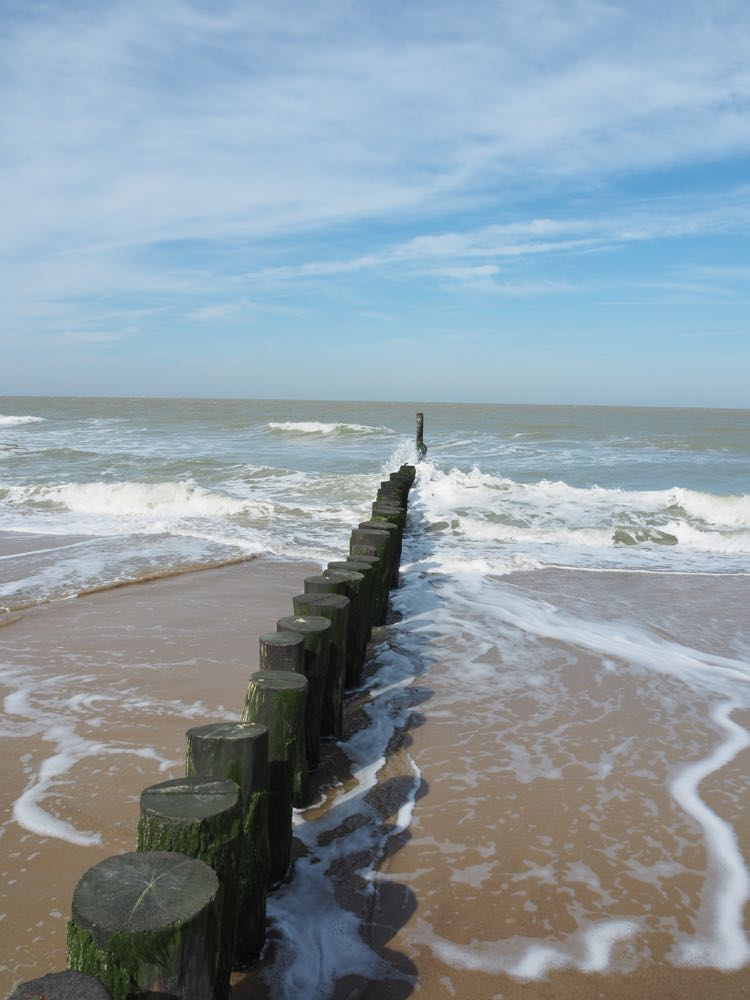 kustlijn met palen in zee en blauwe lucht met sluierbewolking