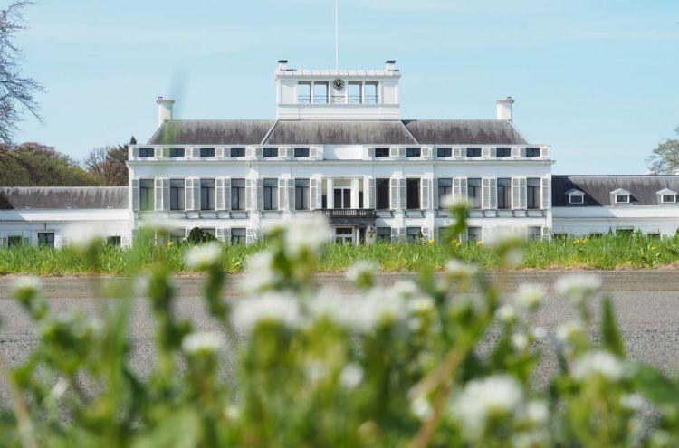 Groot wit gebouw met planten er voor