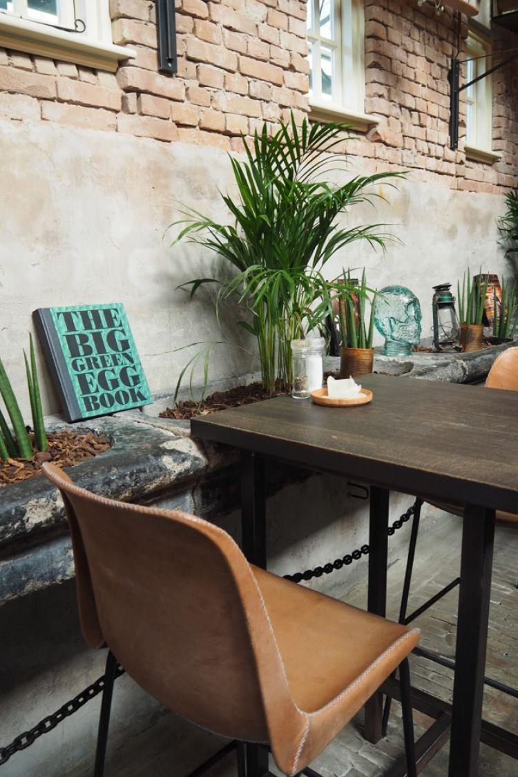 Hoge tafel en stoelen met aan zijkanten planten en borden met quotes