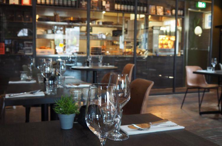 Gedekte tafels met wijnglazen en op de achtergrond een open keuken