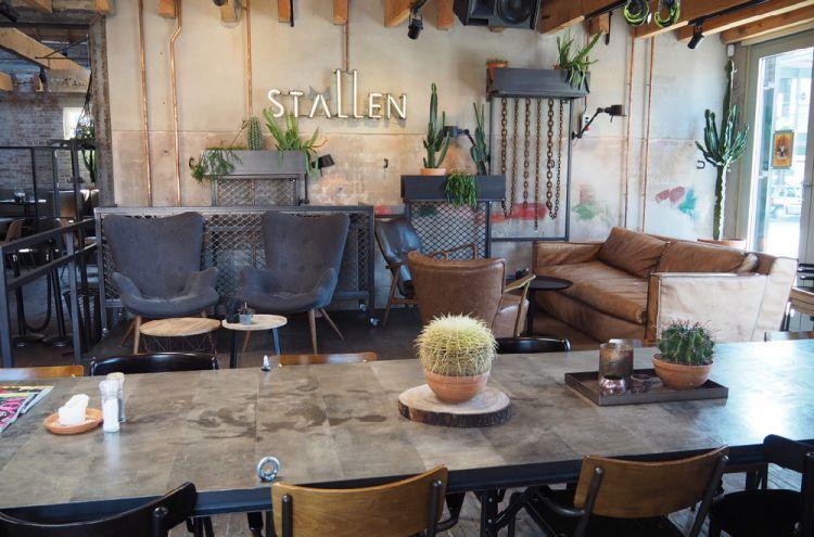 Tafel met stoelen, een cactus erop en aan de wand het woord stallen