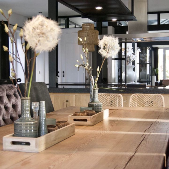Eettafel met vaasjes met bloemen in luxe vakantiehuis