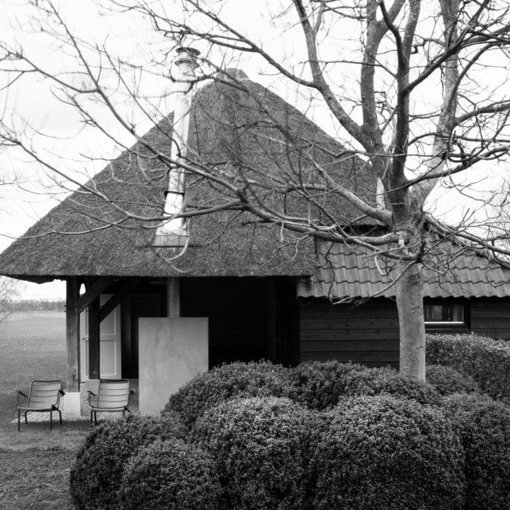 Zwartwit foto van rietgedekt vakantiehuis