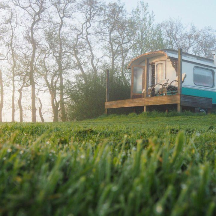 Een nostalgische pipowagen bij ochtendgloren met dauw in het gras