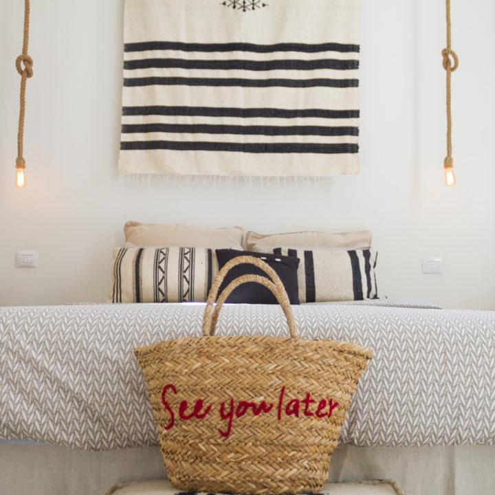 Rieten strandtas aan het voeteneinde van een bed in een B&B kamer