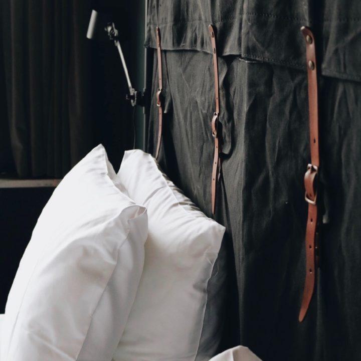 Witte kussens tegen een bedhoofd