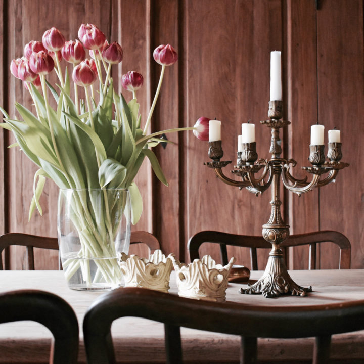 Een bos bloemen een kandelaar op tafel