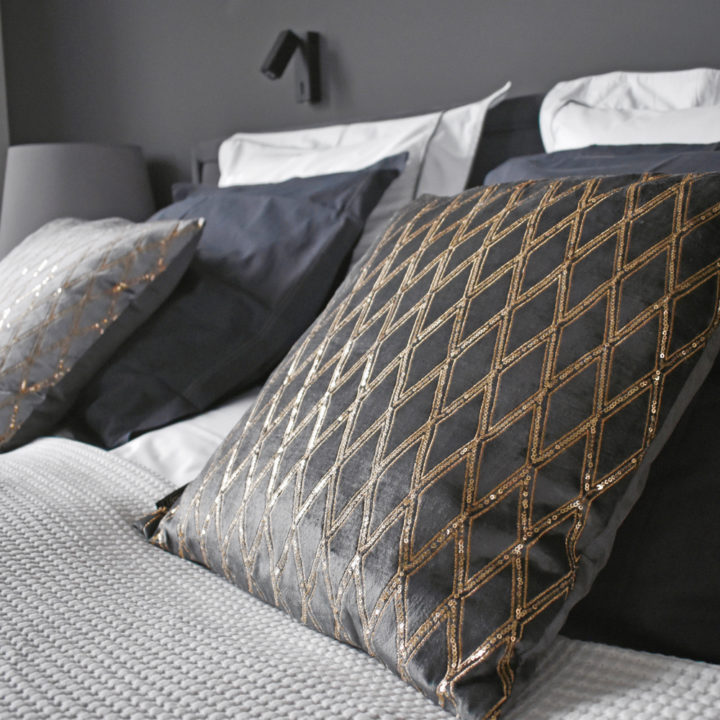 Kussens met een ruitenpatroontje op een opgemaakt bed in de suite Pinot Noir