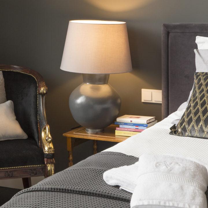 Stapel boeken op nachtkastje naast bed