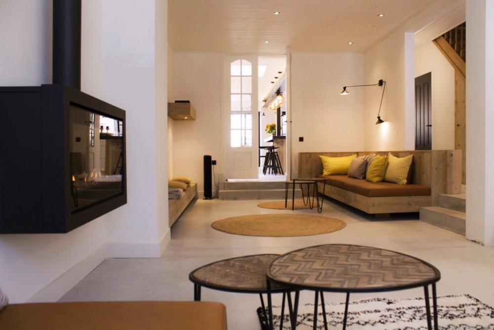 Lichte woonkamer met een haardvuur en makkelijke bank