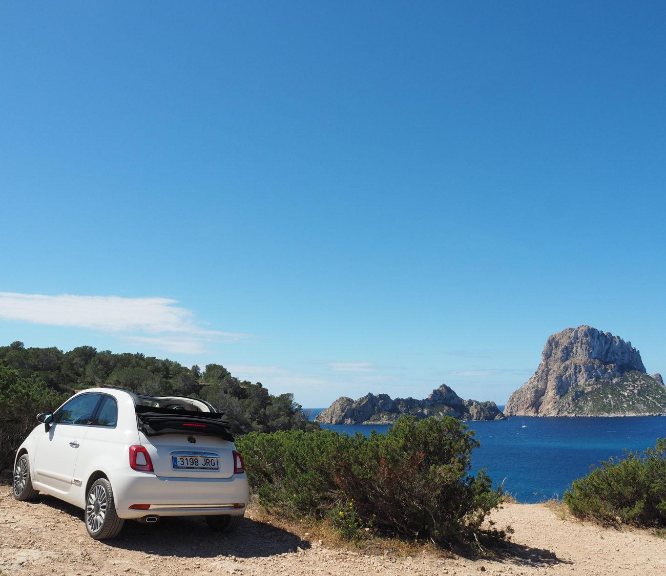 Witte huur auto geparkeerd bij struiken met zee met grote eilanden op de achtergrond