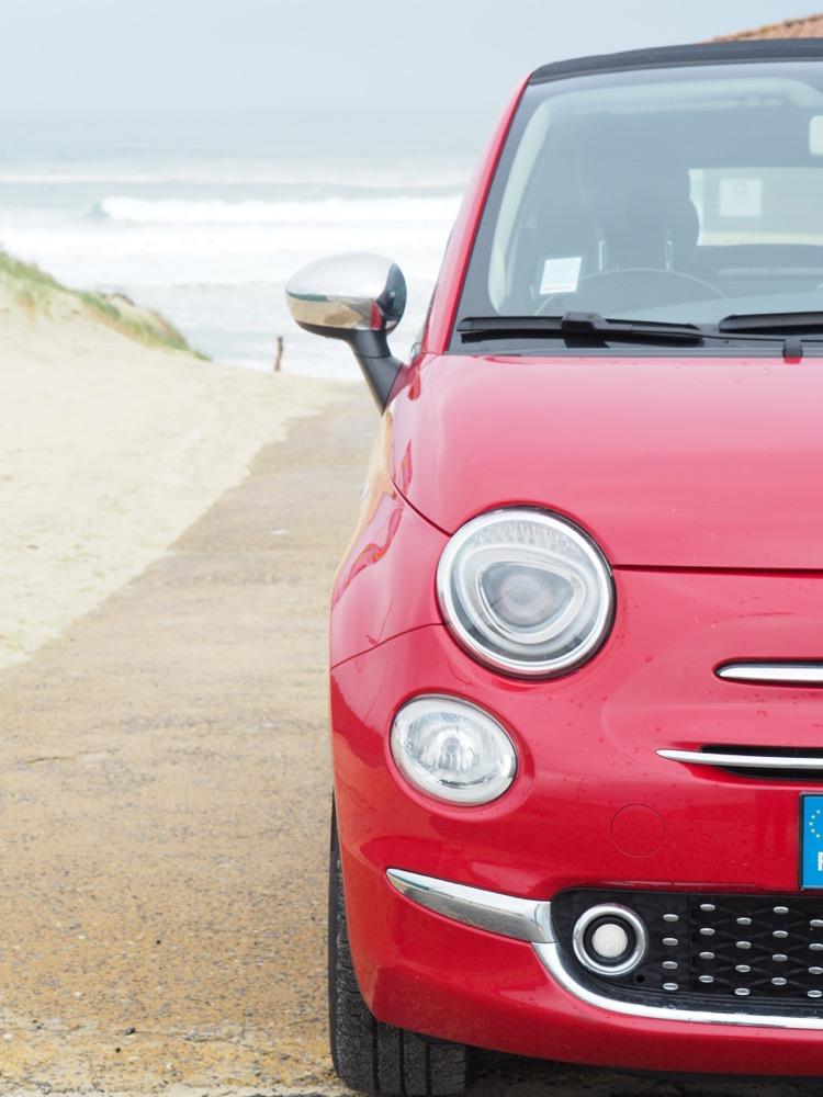 Rode huurauto op het strand