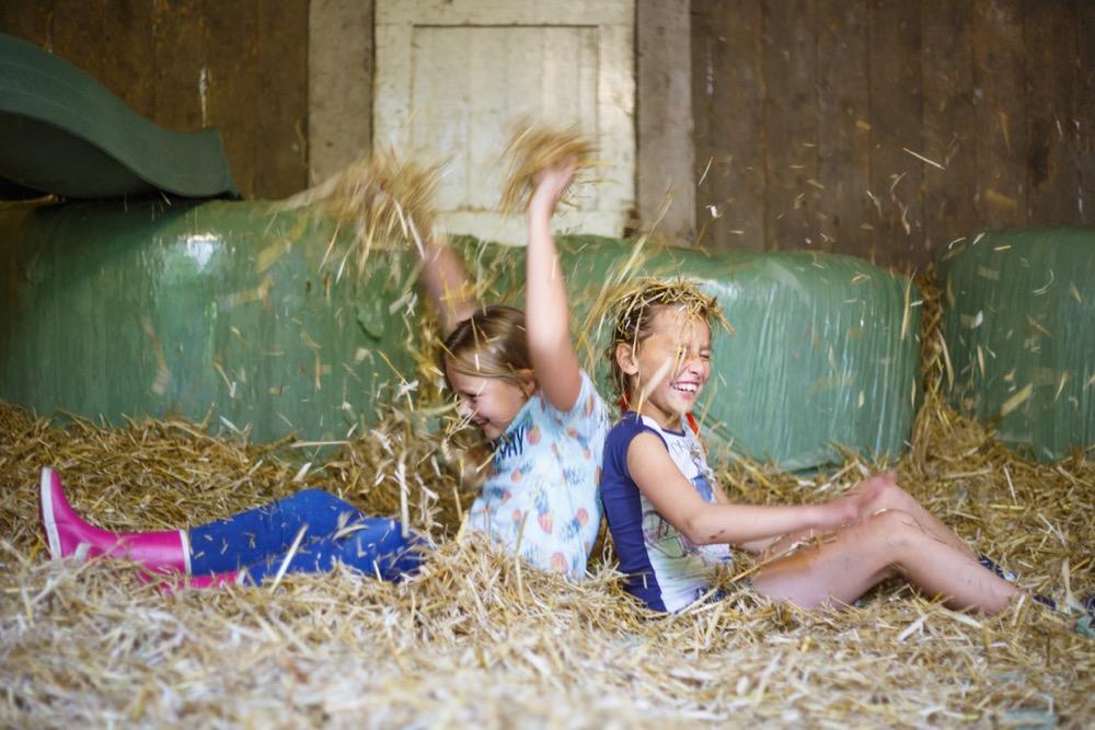 Kinderen spelen in het hooi
