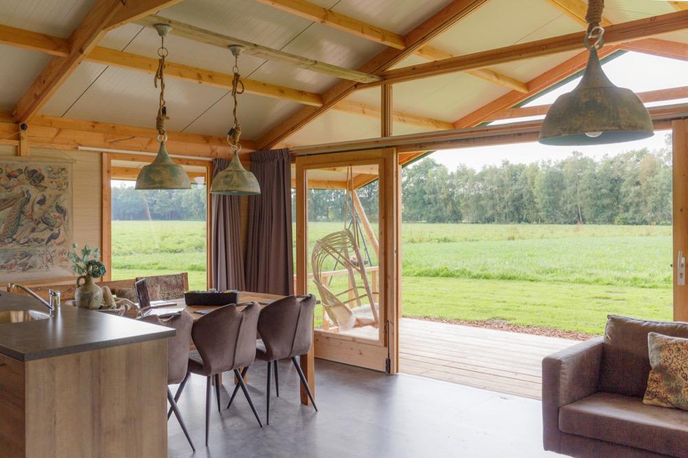 Luxe lodgetent met eethoek en hangstoel in een weiland