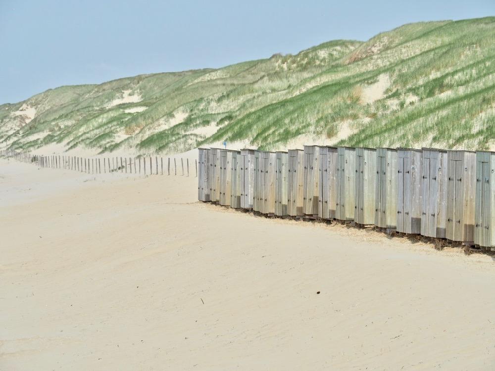 Houten kleedhokjes op de grens tussen de duinen en het strand
