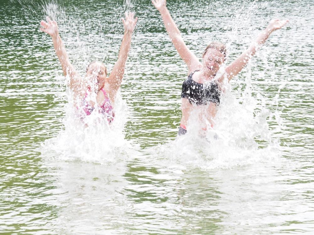 2 meisjes die dikke pret hebben in het water tijdens de vakantie in Europa.