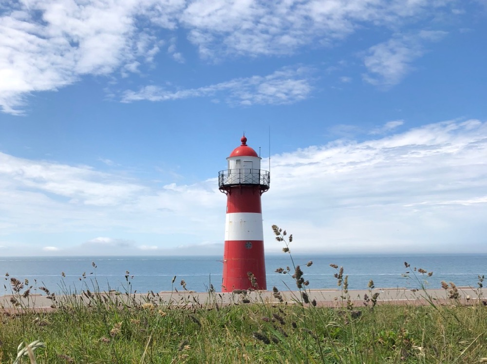 Rood met witte vuurtoren aan de kust van Zeeland
