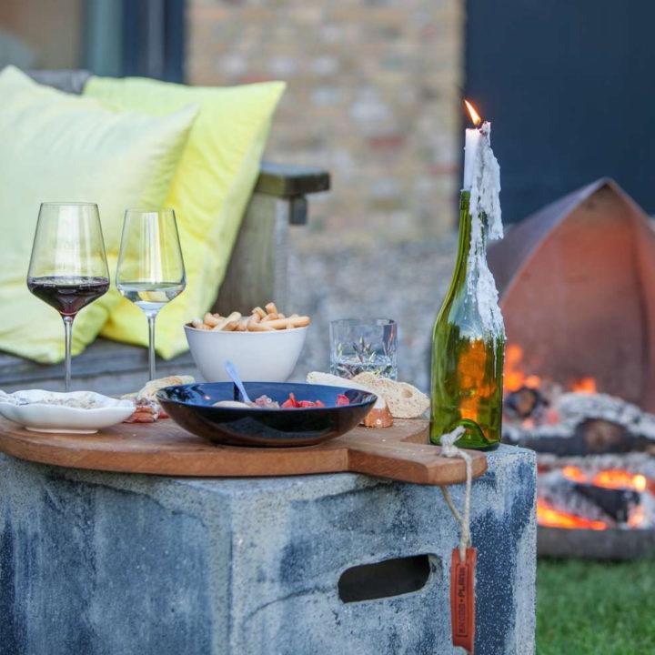 Brandende kaars, glazen wijn, vuurtje en hapjes